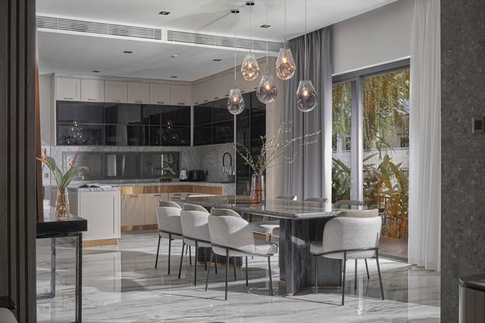 Khu bếp có những đường ốp kim loại trang trí, kết hợp với các phụ kiện thông minh tạo sự tiện nghi. Cửa mặt ngang được mở rộng ngay cạnh bàn ăn nhìn thẳng ra khu vườn.