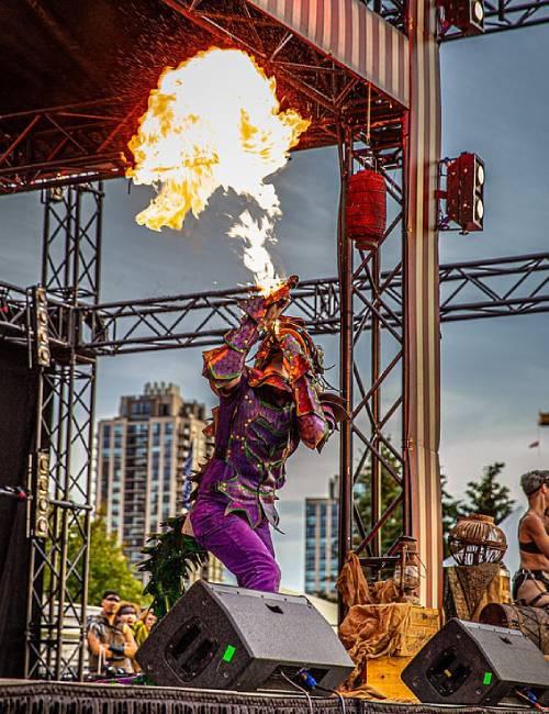 Burns hóa trang thành rồng khi biểu diễn thổi ra lửa trên đường phố. Ảnh: PA Real Life.