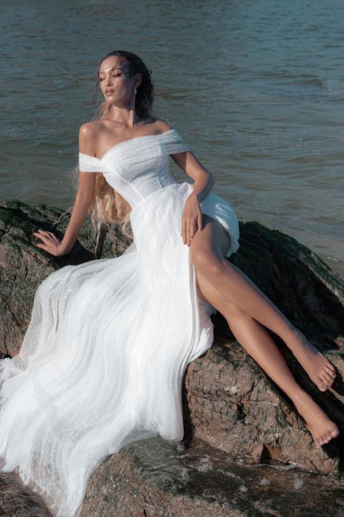 Phom dáng váy gọn gàng, phù hợp với lễ cưới diễn ra ở biển. Chiếc váy chữ A có phần xẻ đùi cao khoe chân dài miên man của cô dâu, thích hợp cho các hoạt động ngoài trời.