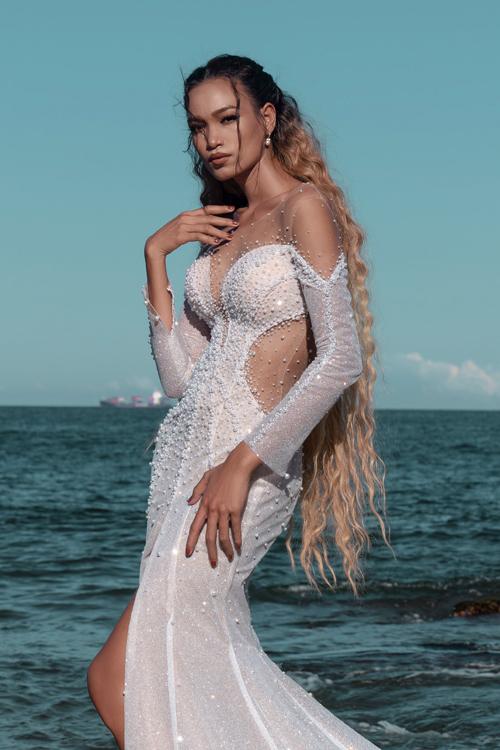 Váy được điểm hạt tạo sự bắt sáng tự nhiên. Cổ illusion được áp dụng để khoe vẻ gợi cảm của cô dâu.