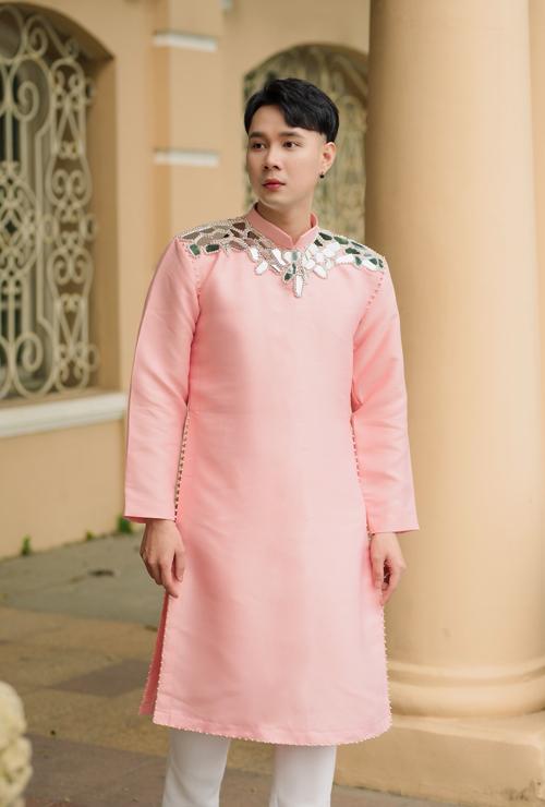 Áo nam được tạo điểm nhấn với các mảnh gương đính hạt, tạo vẻ phá cách và giúp bộ áo dài trơn nổi bật.