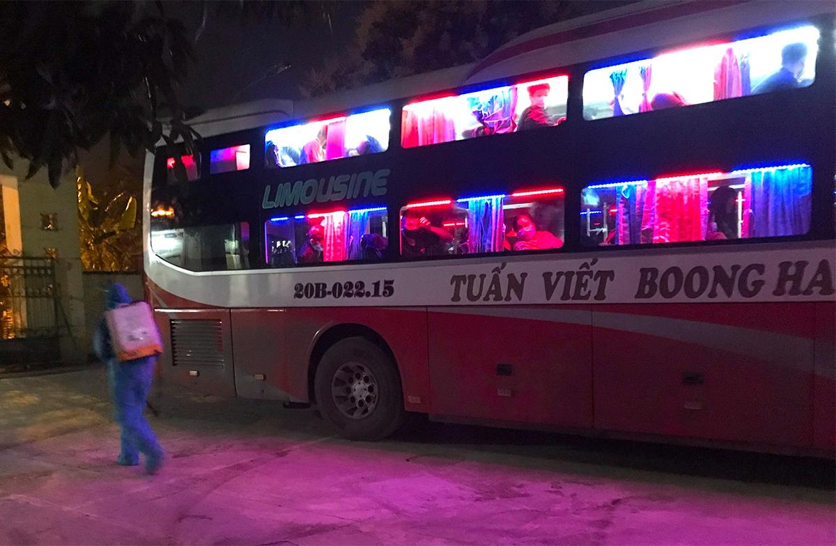 Nhân viên y tế phun khử khuẩn xe khách chở 7 người Trung Quốc. Ảnh: Đình Thanh