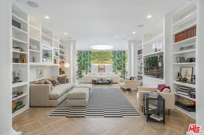 Phòng khách rộng rãi, sang trọng với sàn gỗ, sofa bọc vải lanh trắng và các kệ trang trí hai bên.