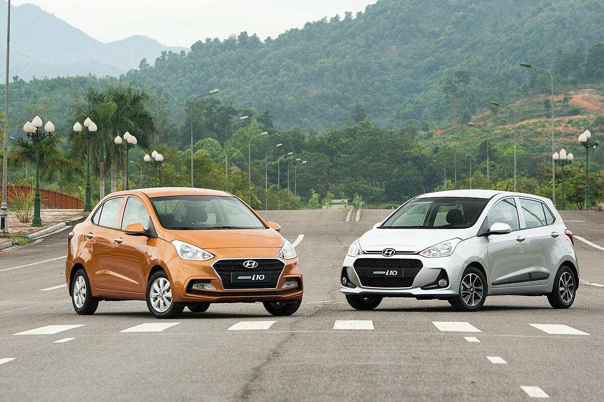 Hyundai Grand i10 với hai biến thể sedan (màu cam) và hatchback (màu ghi bạc).