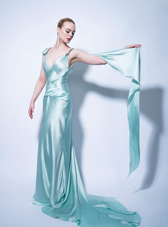 Elle Fanning in a mint green Gucci satin gown with crystal brooches and cape