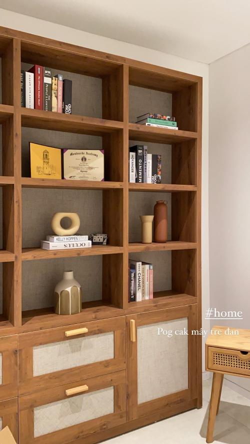 Trong phòng khách, cặp vợ chồng đặt mua tủ gỗ và trang trí với các loại bình gốm, sách.