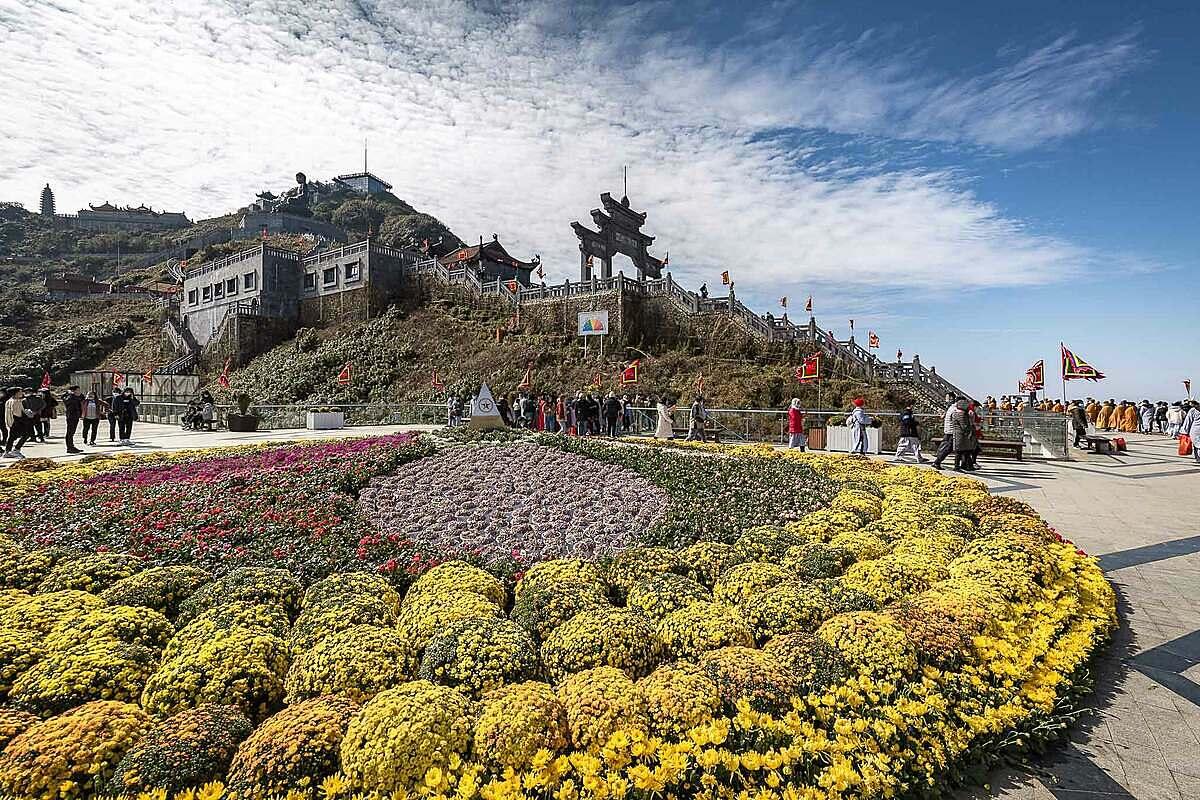 Lên tới sân mây, đại cảnh Vạn hoa dâng Phật được làm từ hoa tươi có diện tích 150m2 cùng bức tường hoa treo chữ Lộc và An không khỏi làm du khách choáng ngợp. Không gian an lạc, thiền tịnh nơi đây khiến mỗi bước chân hành hương bái Phật trên đỉnh Fansipan thêm nhẹ nhàng, an yên.