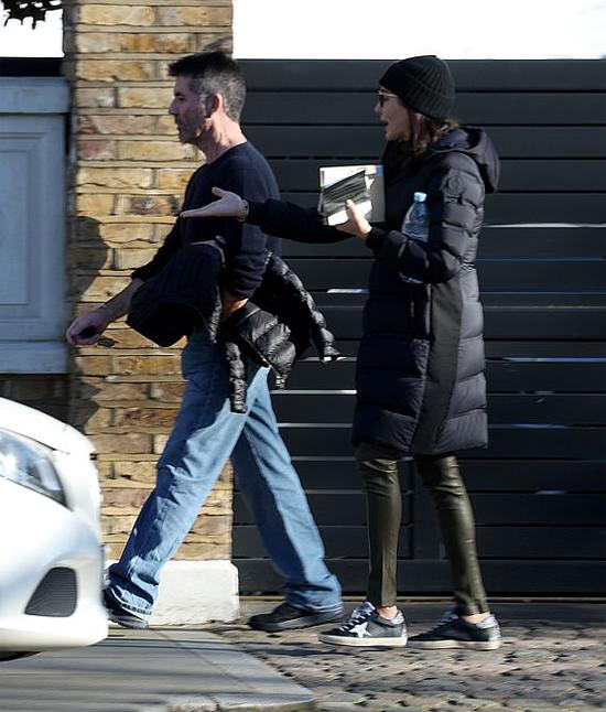 Trên đường phố, Simon Cowell đi trước trong khi bạn gái theo sau, tranh luận căng thẳng về điều gì đó.