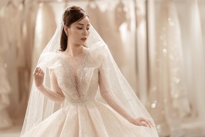 Kỹ thuật dựng phom độc quyền định hình vòng eo con kiến cho nàng dâu và chi tiết xếp ly của tùng váy khiến cô dâu trông cao, thanh thoát hơn.