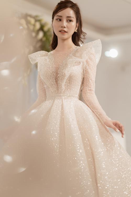 Trần Hạnh mang vẻ đẹp dịu dàng, trong sáng của một cô gái Á đông nên NTK Phương Linh đã lựa chọn dáng váy bồng bềnh công chúa cho cô. Váy có dáng tay dài thanh lịch và sang trọng.