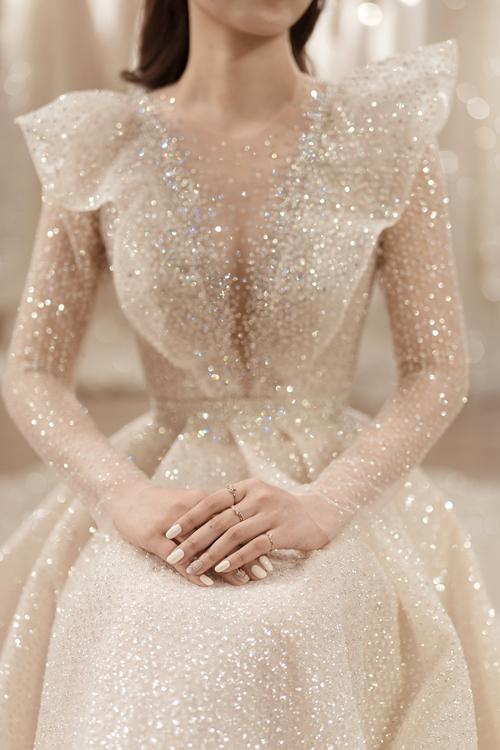 Hàng nghìn viên pha lê bắt sáng tạo hiệu ứng tán sắc, khiến chiếc váy cưới trắng lại trở thành sắc màu cầu vồng lung linh, huyền ảo.