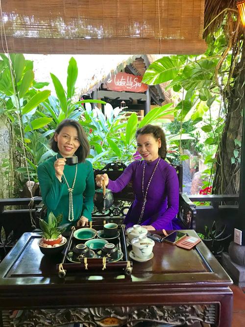 Cô Ngọc Hương (áo tím) và em gái chọn phụ kiện ngọc trai đồng điệu khi diện áo dài và thưởng trà trong không gian xanh mát.