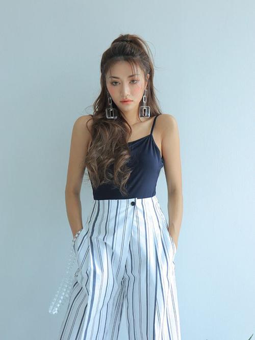 Quần lưng cao hoạ tiết kẻ sọc đi cùng áo thun hài hoà màu sắc sẽ giúp bạn gái tôn chiều cao hiệu quả.