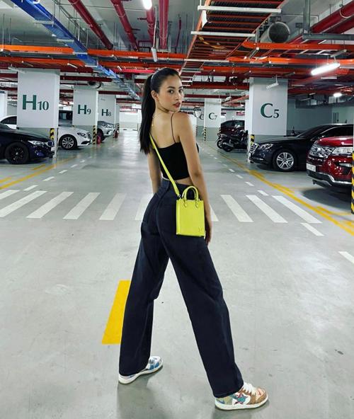 Đi mua sắm với set đồ đơn giản gồm áo hai dây, quần jeans ống suông, Tiểu Vy chọn túi tông vàng neon để tạo điểm nhấn.