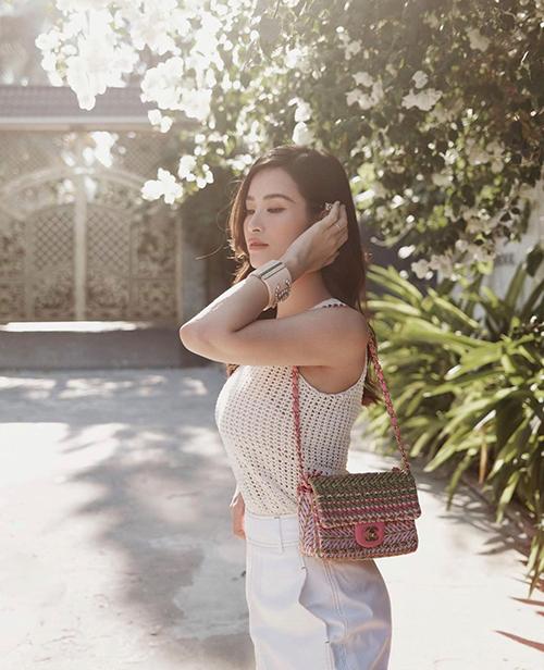 Diện áo lưới gam màu đồng điệu cùng quần lưng cao, Đông Nhi chọn thêm túi đan thủ công của Chanel để mix đồ.