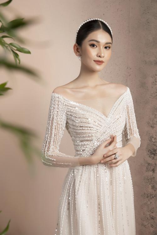 Cô dâu khoe khéo vòng một sexy với tay áo trễ nải. NTK cũng khéo léo may vải voan mỏng trước ngực để giữ sự an toàn cho trang phục.