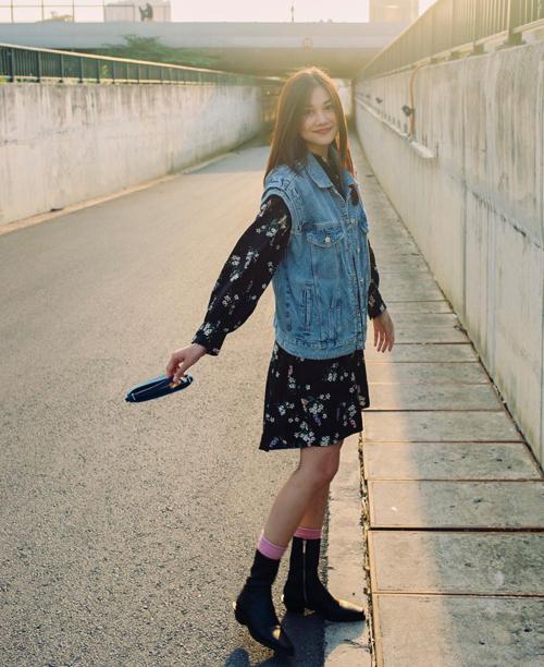 Lối phối đồ đơn giản của Thanh Hằng dễ áp dụng cho nhiều bạn gái. Jacket jeans kiểu sát nách được mix cùng váy hoa nhẹ nhàng. Phụ kiện bốt cổ ngắn trẻ trung và phù hợp khi di du lịch ở xứ lạnh.