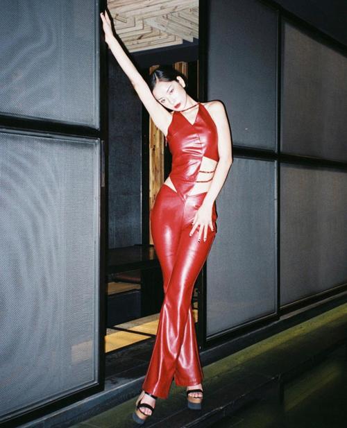 Áo bất đối xứng và quần ôm bó sát thiết kế trên chất liệu da bóng được Chi Pu sử dụng cùng sandal đế thô để tôn vẻ đẹp hình thể.