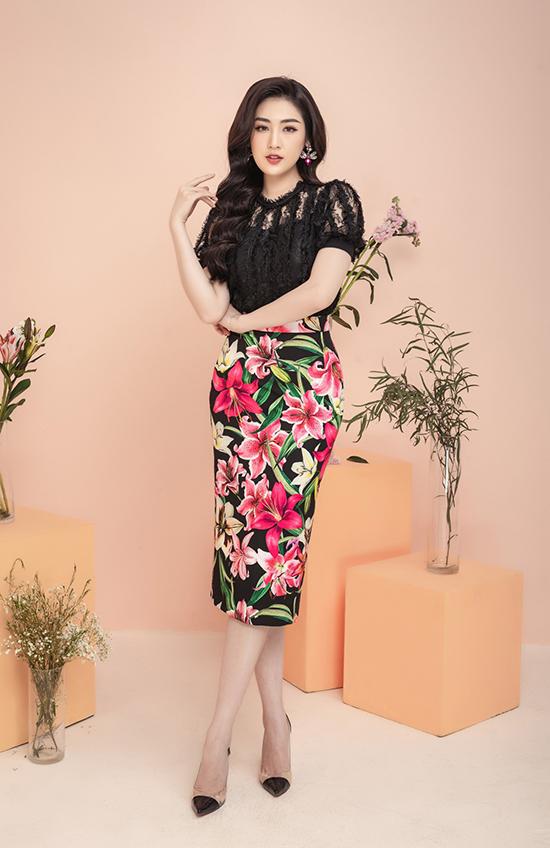 Á hậu kết hợp trang phục với khuyên tai màu đồng điệu với họa tiết của chân váy và tóc xoăn để hoàn thiện phong cách nữ tính, thanh lịch.