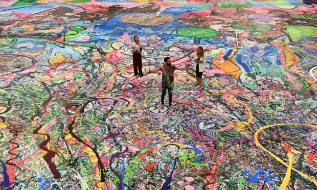 Nghệ sĩ Sacha Jafri (giữa) đứng trên bức tranh kỷ lục của mình tại thành phố Dubai. Ảnh: AFP.
