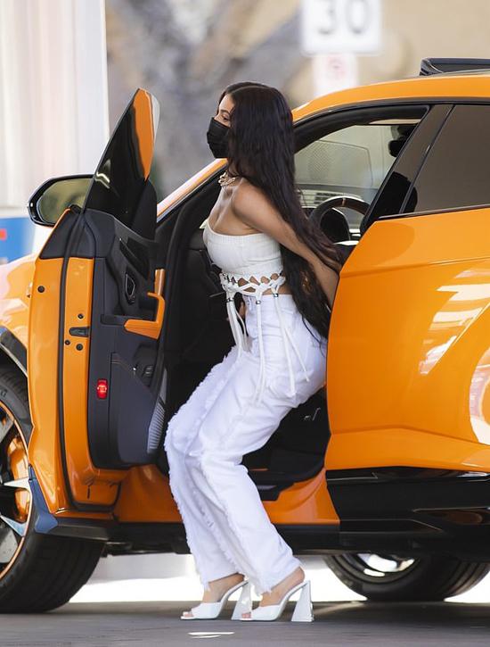 Vào buổi trưa, Kylie Jenner lái chiếc Lamborghini Urus màu cam đi công chuyện. Cô xuất hiện với phong cách quyến rũ, điệu đà, tóc dài thả chấm hông.