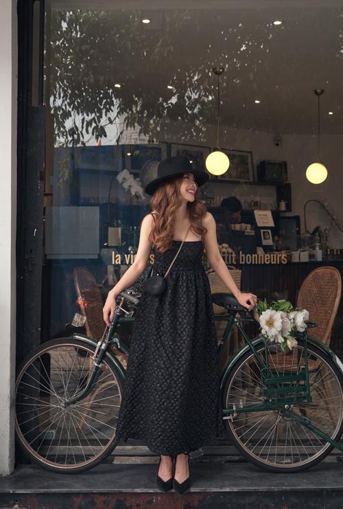 Đầm hai dây tông đen sẽ tránh được cảm giác đứng tuổi bởi họa tiết hoa nổi trang trí khắp thân váy.