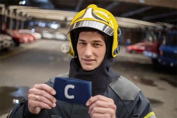 Anh lính cứu hỏa Djordje Vukicevic chụp ảnh kỷ niệm với tấm băng đội trưởng bị CR7 ném trên sân. Ảnh: Reuters.