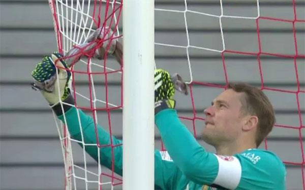 Thủ môn Neuer dùng khăn buộc lại vết rách trên lưới. Ảnh: Digisport.