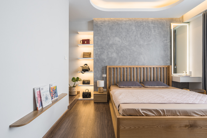 Phòng ngủ tối giản của cặp vợ chồng. Trong phòng có mảng tường sơn hiệu ứng giả xi măng bắt trend. Một hệ tủ kệ được bố trí để nữ gia chủ đựng túi xách. Trong phòng có cả bàn trang điểm gắn đèn led, một kệ sách gắn tường để đựng tạp chí.