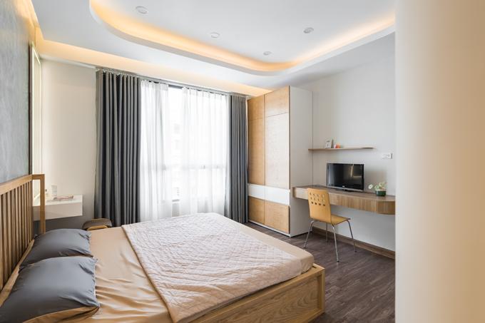 Căn phòng đón nắng nhờ cửa sổ lớn. Phía đối diện giường ngủ là một kệ đựng TV và một tủ đựng quần áo.