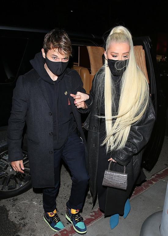 Xtina nắm tay bạn trai vào nhà hàng.