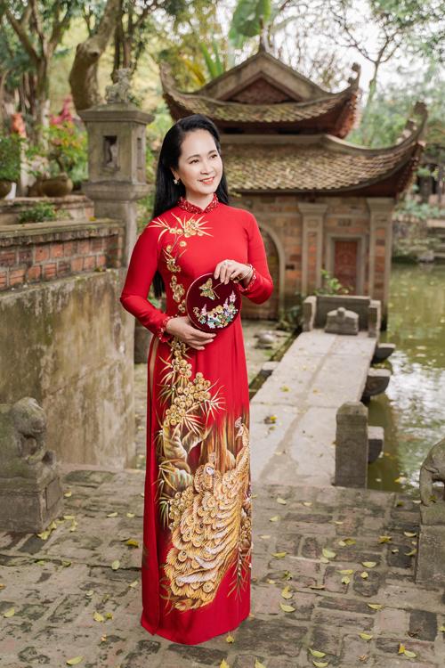 Tà áo dài gam đỏ với họa tiết chim công màu đồng giúp mang đến sự quý phái cho người diện, gợi nhắc về các nét đẹp truyền thống xưa.