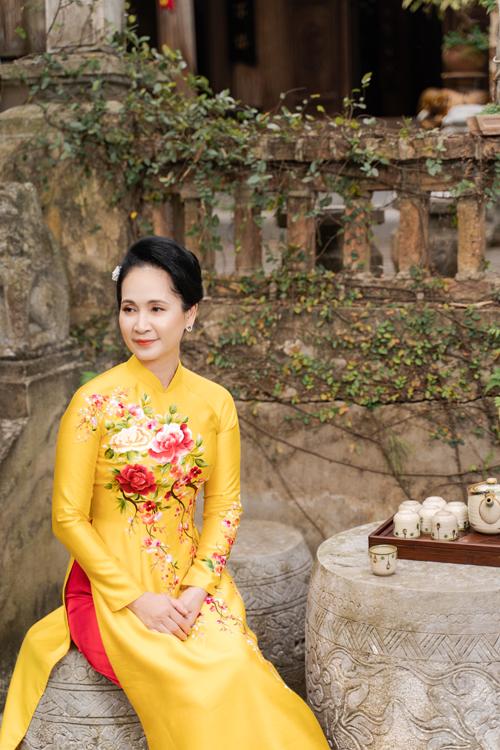 Màu vàng cũng là gam màu phổ biến trong việc lựa chọn áo dài của phụ nữ trung niên. Họa tiết hoa dây leo trải dài giúp giảm sự chú ý nơi vòng hai và tạo điểm nhấn nhã nhặn.