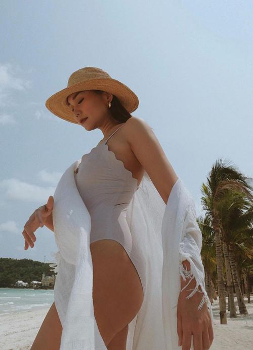 Khi diện monokini trắng, Thanh Hằng phối thêm khăn choang và mũ nan hợp xu hướng mùa hè.