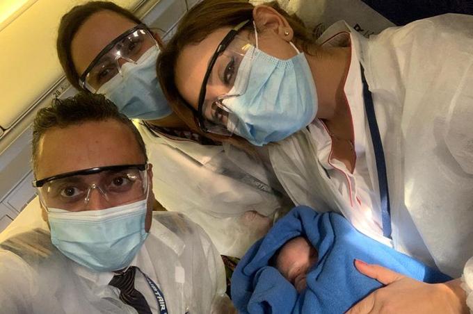 Các thành viên phi hành đoạn chụp cùng em bé sơ sinh. Ảnh: Facebook.