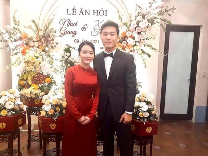 Trong một tấm ảnh mới được lan truyền về đám hỏi kín tiếng, cô dâu Nhuệ Giang đã diện áo dài đỏ trơn cổ thấp bên chú rể Xuân Trường.
