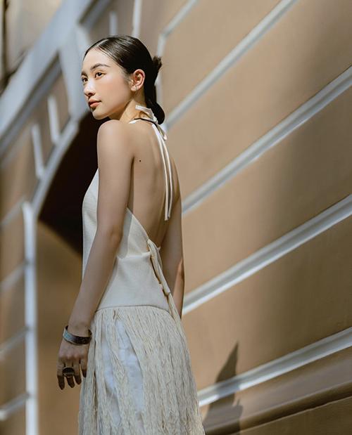 Jun Vũ khoe vai gầy mong manh và toàn bộ lưng trần với áo cổ yếm trang trí tua rua từ sợi dệt mộc.