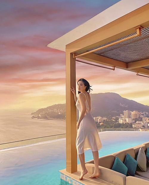 Đầm hai dây vải lụa trắng giúp Bảo Thy khoe lưng trần gợi cảm và chụp ảnh so deep với khung cảnh ráng chiều trên biển.