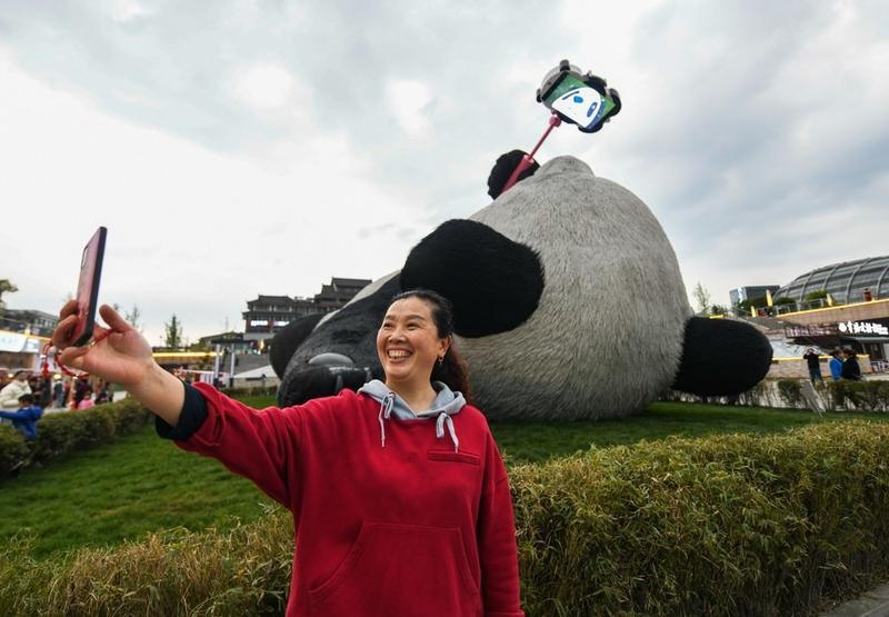 Du khách thích thú chụp ảnh với Selfie Panda hôm 7/4, vài ngày sau khi chú gấu trúc khổng lồ ra mắt với công chúng, nhanh chóng trở thành điểm du lịch nổi tiếng.