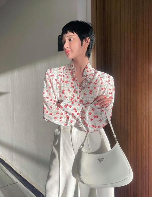 Quần lưng cao, sơ mi cổ điển in họa tiết dâu tây và túi xách tay tông trắng là những món đồ được Hiền Hồ kết hợp ăn ý khi xuống phố.
