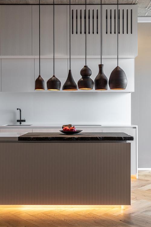 Bếp được đặt ở khu vực trung tâm. Đảo bếp từ đá granite có thêm đèn từ các loại bình gốm khác nhau tạo sự vui tươi cho căn bếp.
