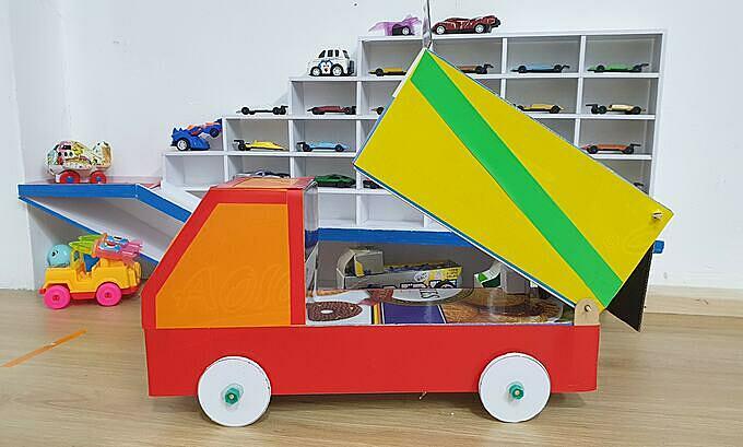 Xe tải ben làm từ vỏ mực máy in và kệ trưng bày ô tô cho con trai làm từ nhựa Formex.