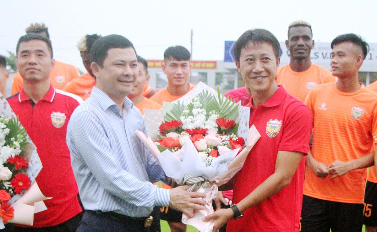 Phó chủ tịch UBND tỉnh Hà Tĩnh, ông Lê Ngọc Châu (áo trắng), tặng hoa cho HLV Thành Công tại buổi ra mắt, chiều 15/4. Ảnh: Hùng Lê