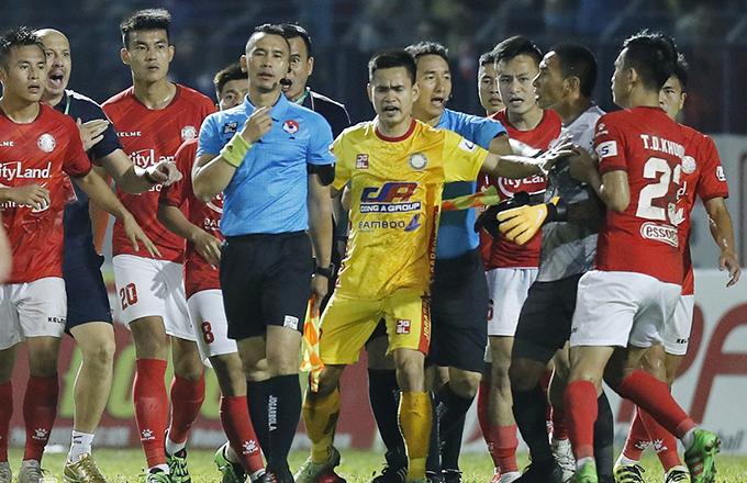 Thủ môn Thanh Thắng cùng các cầu thủ và ban huấn luyện TP HCM quây trợ lý trọng tài Nguyên Thành sau trận đấu với Thanh Hóa. Ảnh: LT.