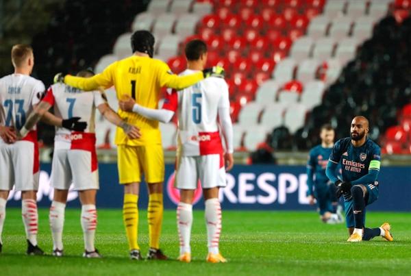 Thủ quân Arsenal Lacazette quỳ gối, nhìn chằm chằm vào dàn cầu thủ Slavia Prague. Ảnh: EPA.