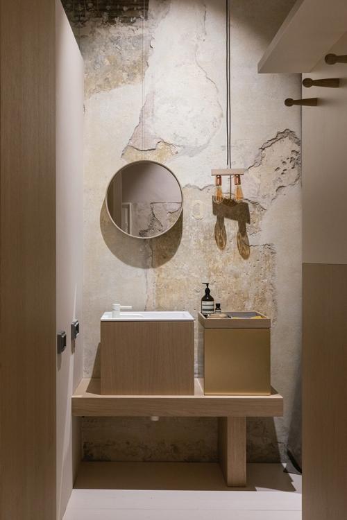 Phòng vệ sinh bên cạnh cũng có các mảng tường gạch loang lổ, được chọn nội thất gỗ tối giản.