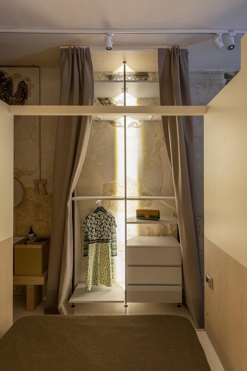 Đối diện giường ngủ là tủ quần áo, được ngăn lại với khu vực khác bởi rèm.