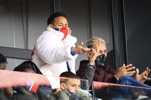 Neymar mặc áo lông trắng muốt ngồi trên khán đài. Ảnh: AFP.