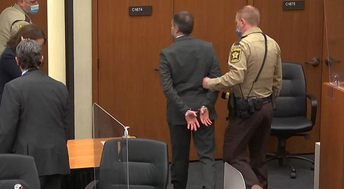 Derek Chauvin bị còng tay ra khỏi toà án hôm 20/4. Ảnh: Reuters.