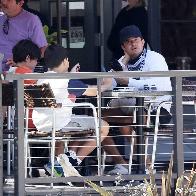 Orlando Bloom cũng được trông thấy dành thời gian riêng cho con trai Flynn (áo trắng xám). Hai bố con ngồi uống nước tại một quán cafe ở Montecito. Flynn là con của Orlando với vợ cũ - siêu mẫu Miranda Kerr.